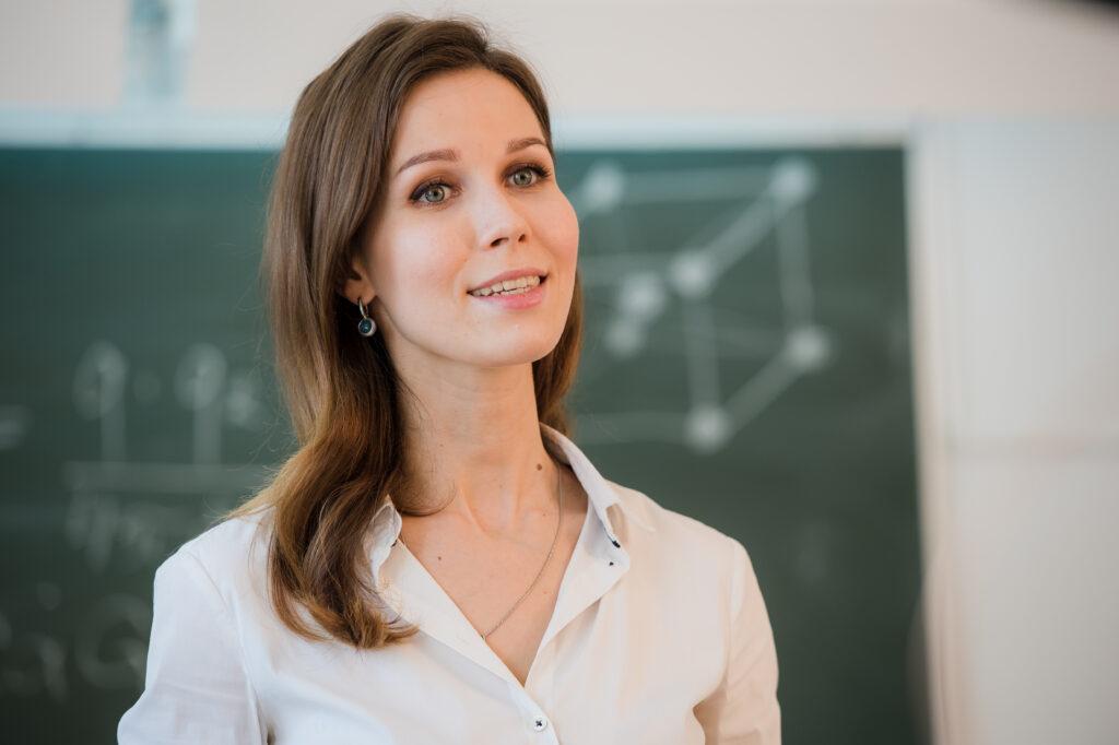 Portrait of happy teacher standing in front of black board.